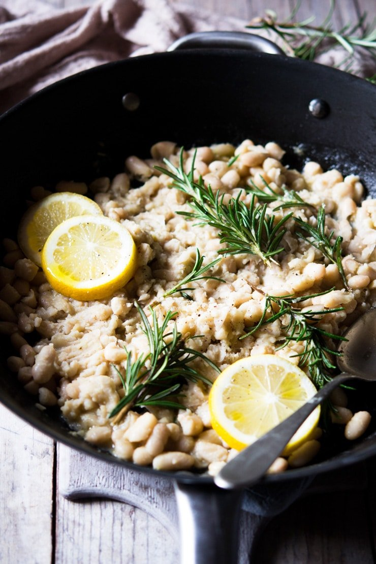 Cannellini bean mash in a large pan with lemon and rosemary