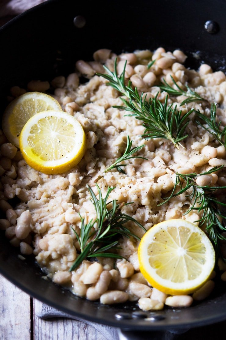 A close up of cannellini bean mash topped with sprigs of rosemary and slices of lemon in a large pan