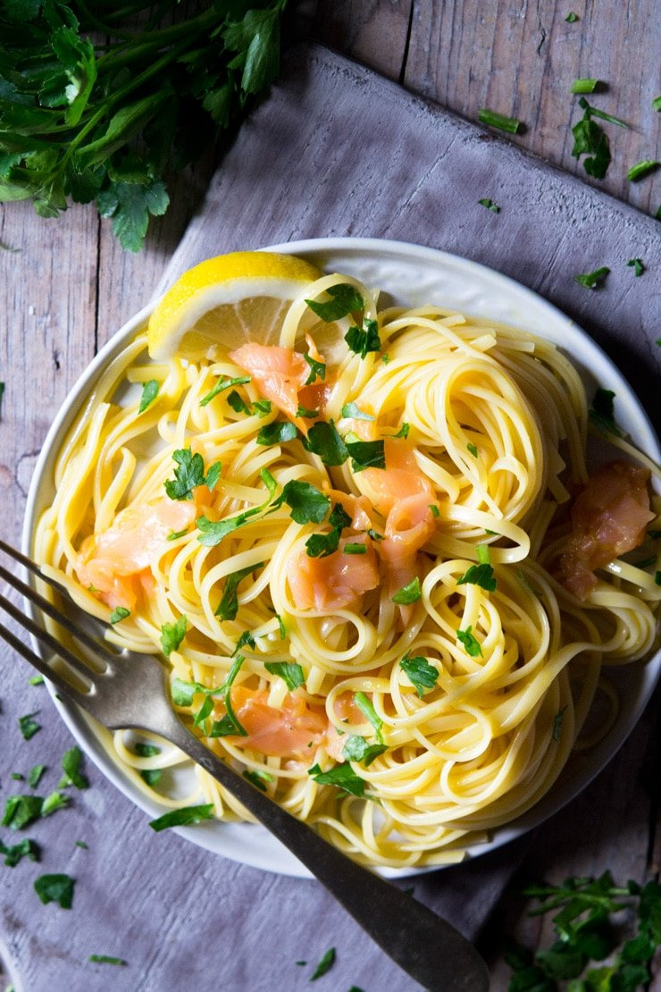 a close up of smoked salmon pasta on a plate and sitting on a wooden surface