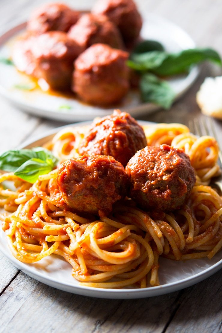 Three mozzarella stuffed meatballs on a plate of spaghetti