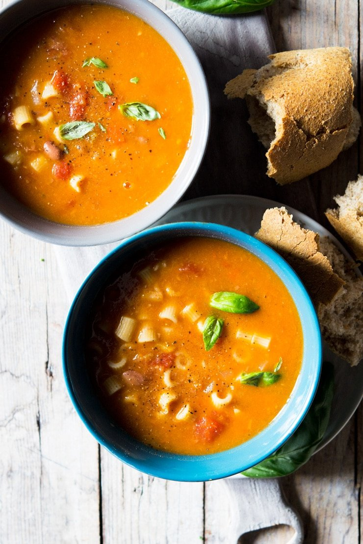 pasta fagioli soup in two bowls with torn crusty bread