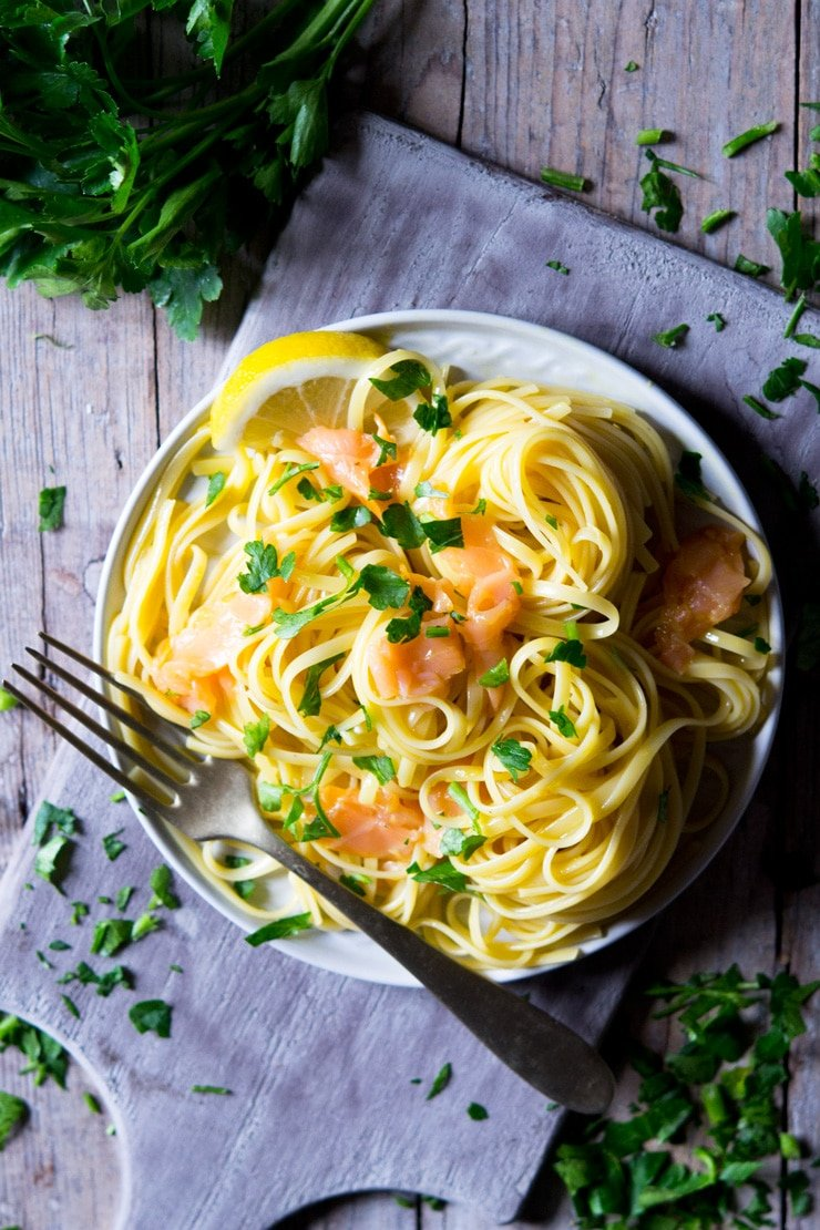 An overhead shot of smoked salmon pasta on a plate with chopped parsley on top