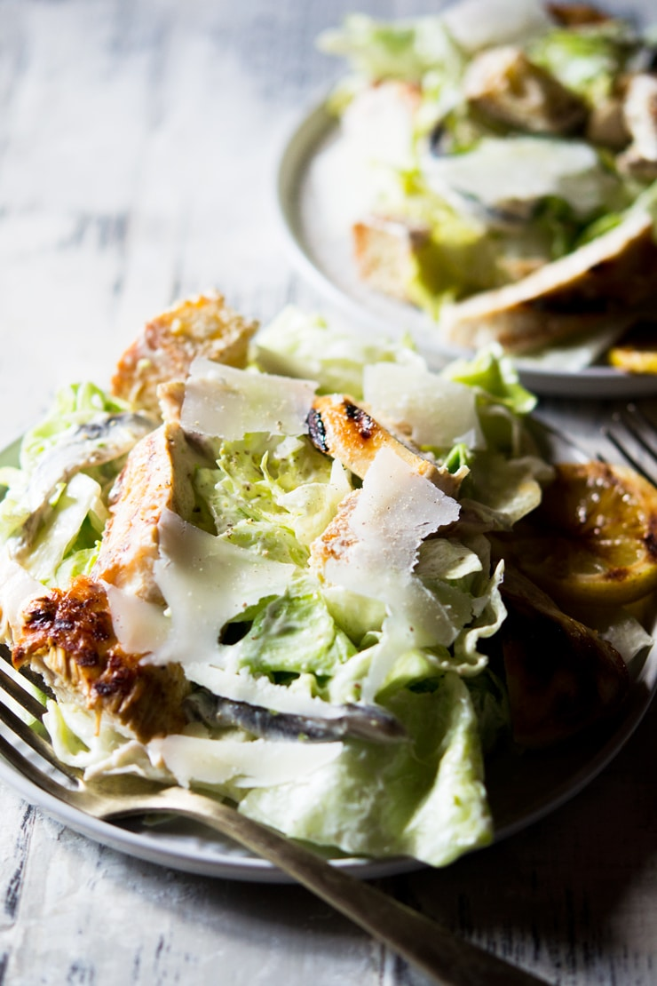 A side shot of a grilled chicken caesar salad on a white plate topped with shavings of parmesan cheese