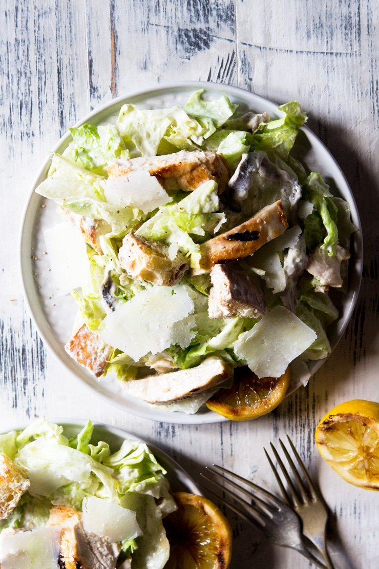 an overhead shot of a grilled chicken caesar salad on a wooden surface
