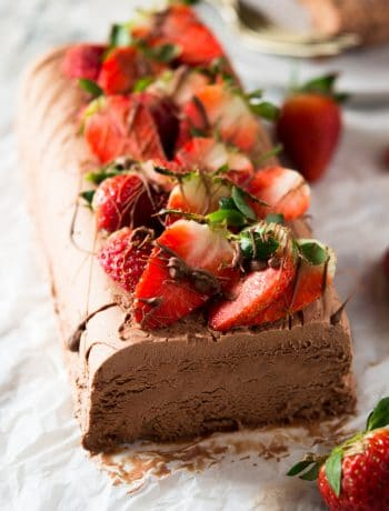A chocolate semifreddo recipe on a white surface topped with fresh berries