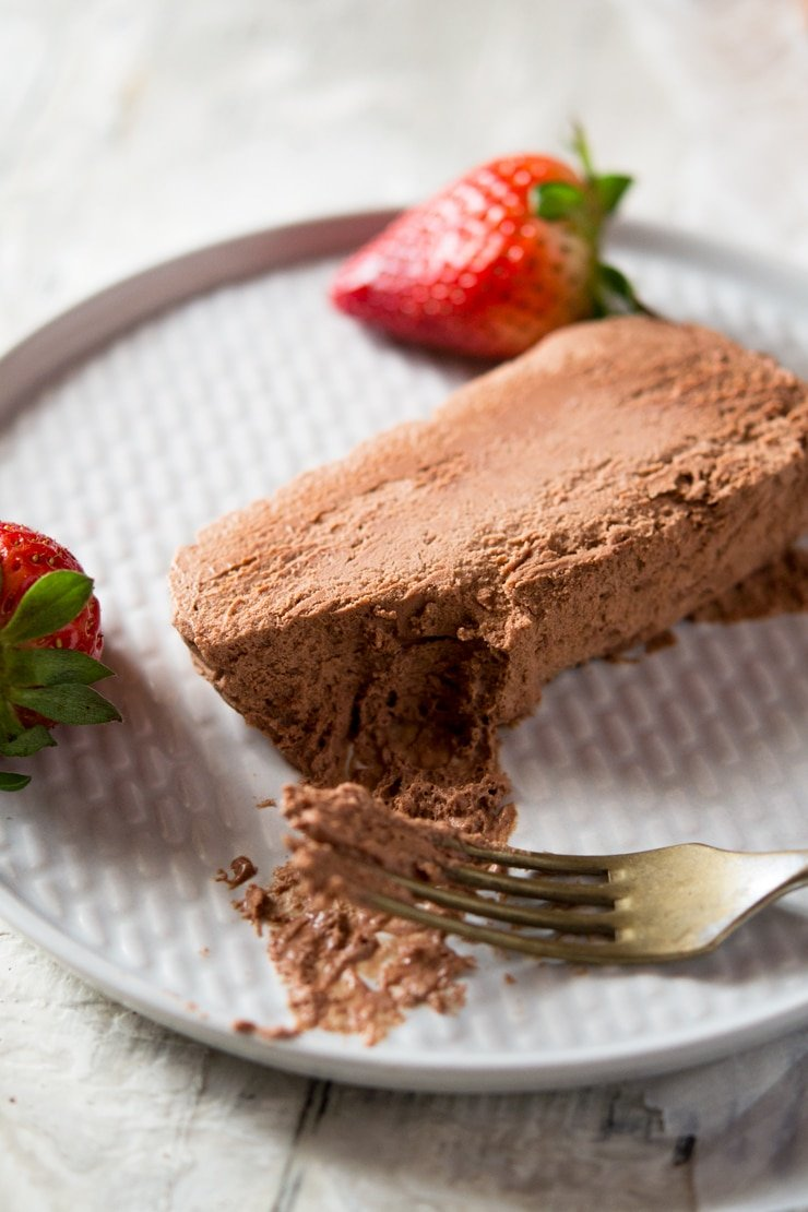 A close up of a slice chocolate semifreddo on a plate with a bite on a fork, an easy semifreddo recipe