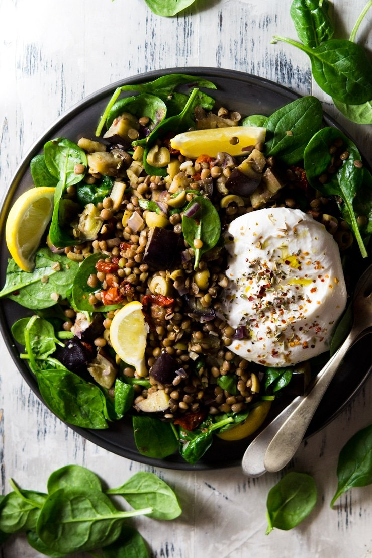 An overhead shot of an Italian lentil salad with eggplant and burrata cheese on a pewter plate