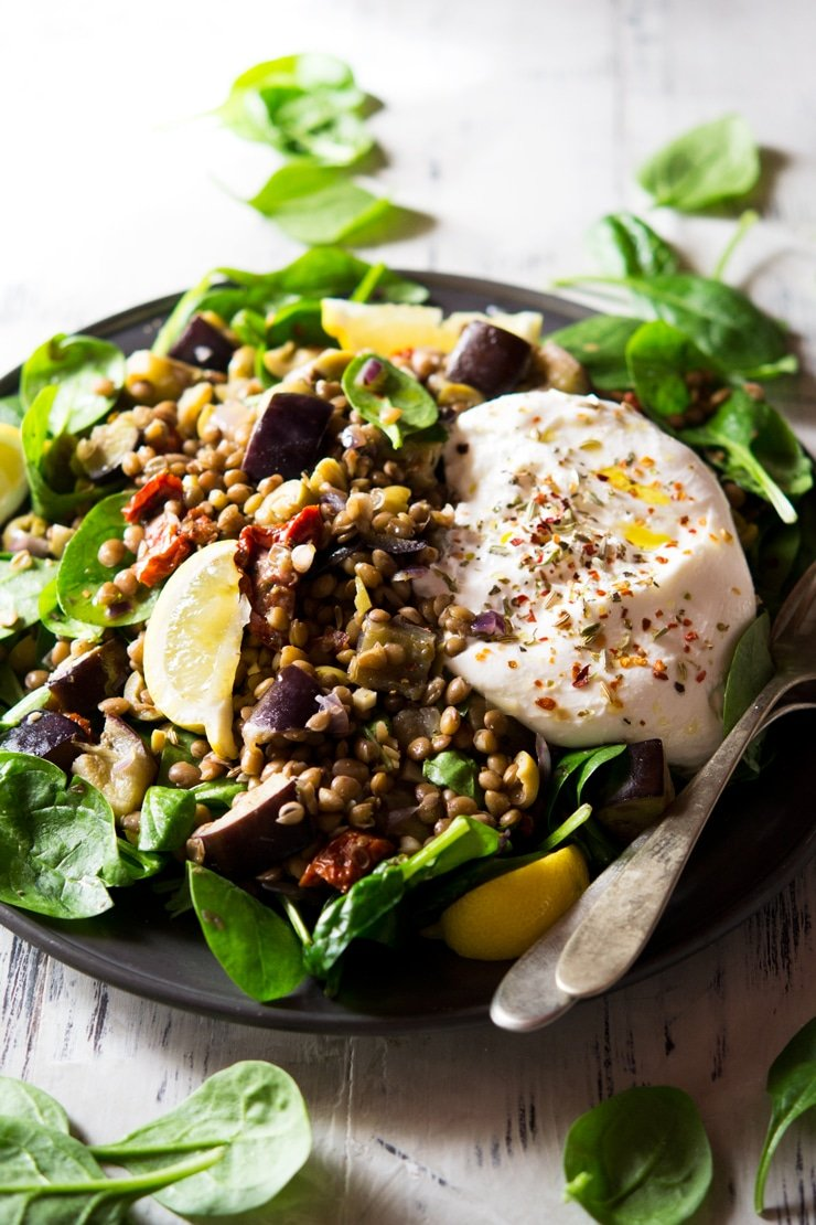 A close up of lentil salad with eggplant and burrata on a plate topped with herbs and spices