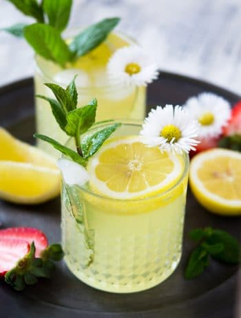 a limoncello cocktail garnished with mint and dasies