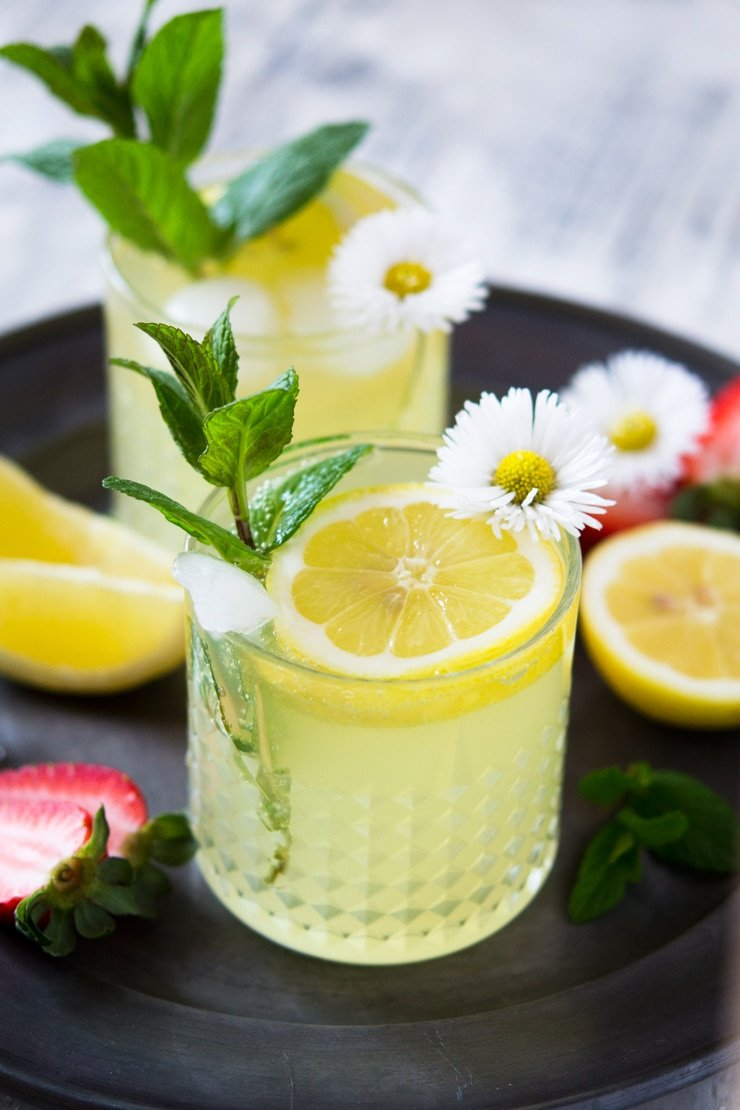 A photo of a limoncello cocktail on a pewter plate garnished with mint leaves and daisies