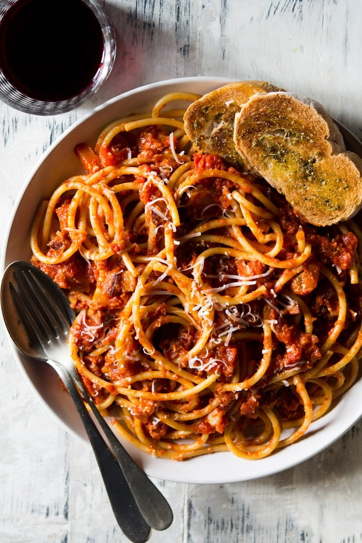 An overhead shot of pasta amatriciana in a bowl with crusty bread