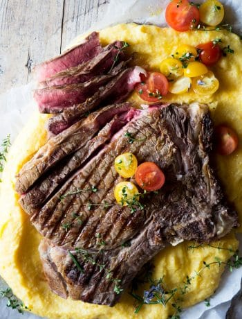 A florentine steak on a bed of polenta with some herbs