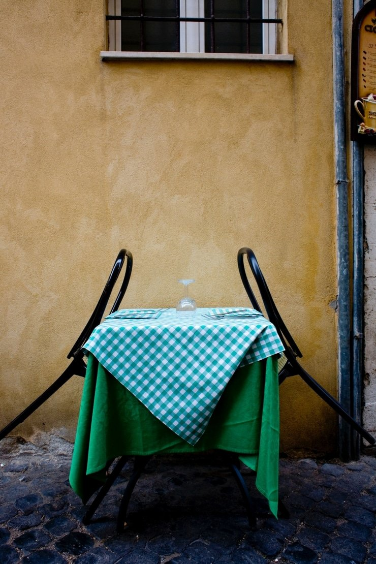 A photo of a yellow outside wall of a building with a table with a green checkered tablecloth and two back seats