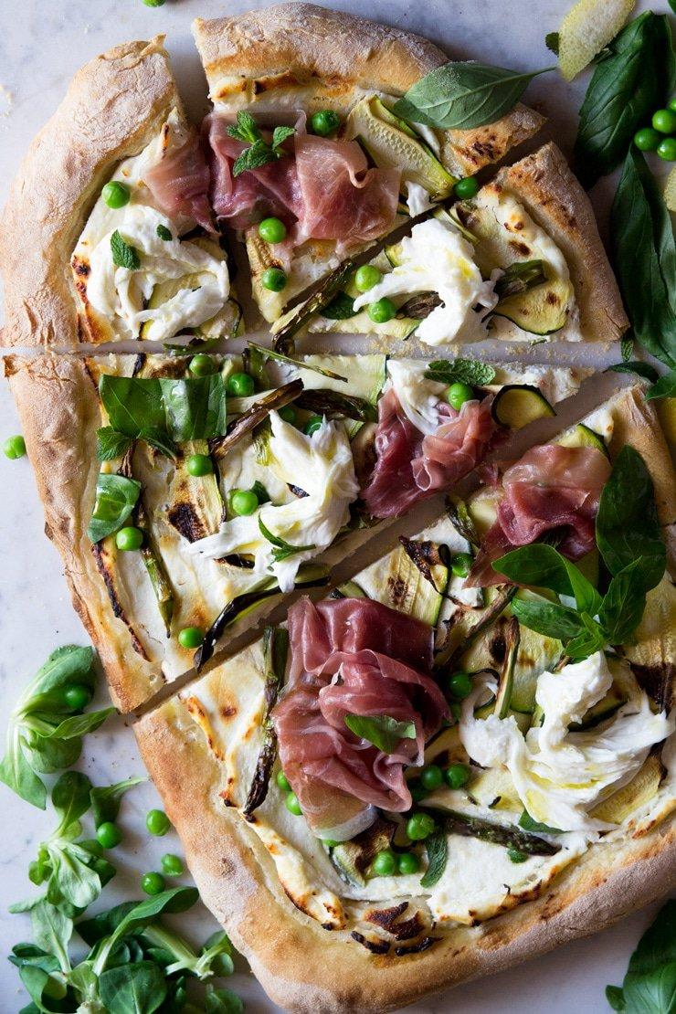 An overhead shot of a white base pizza with zucchini, prosciutto and asparagus