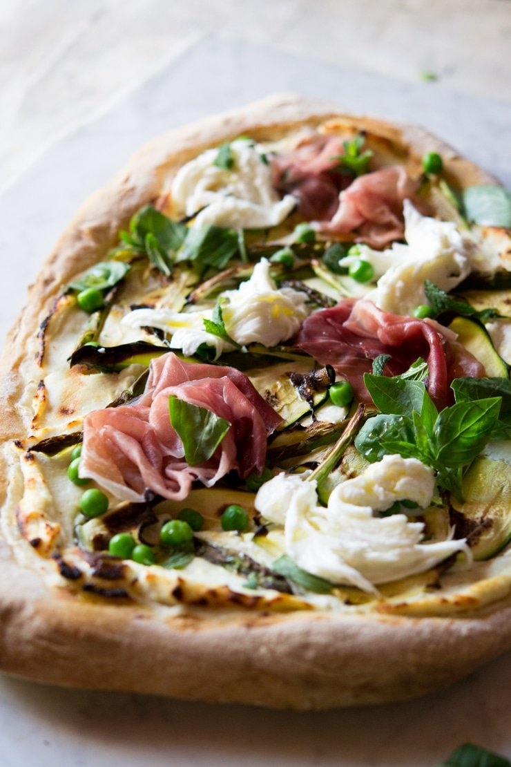 A close up of pizza with zucchini, asparagus and prosciutto