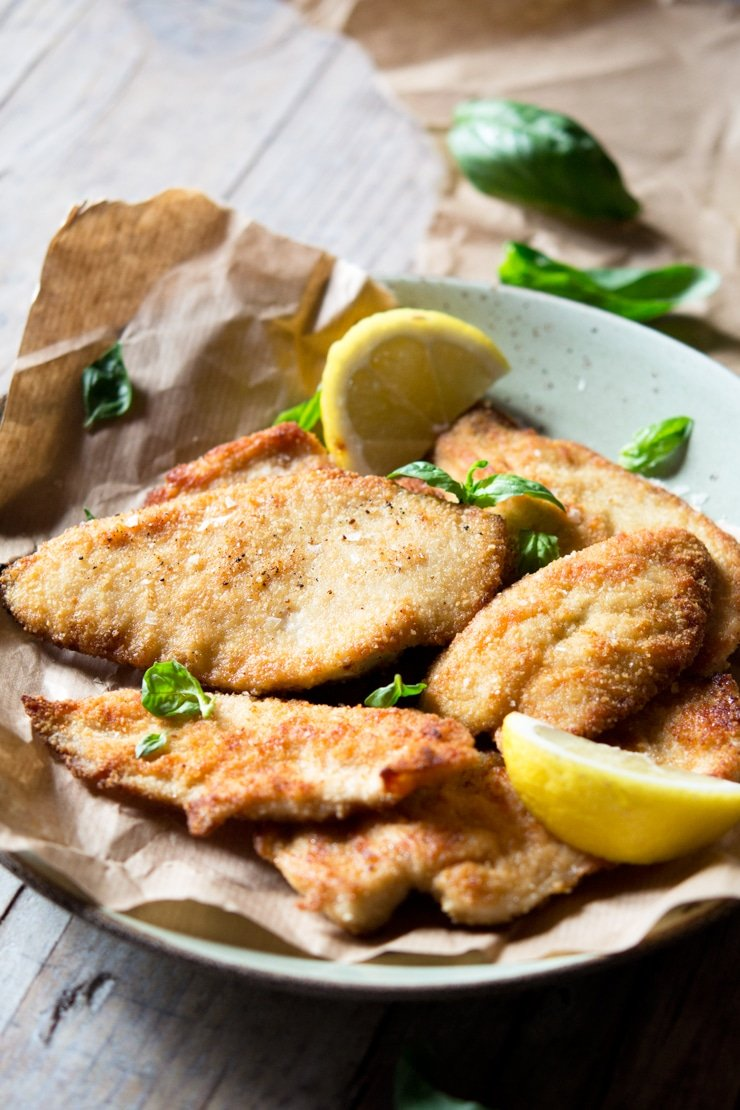 A side shot of breaded chicken cutlets on a plate with lemon wedges