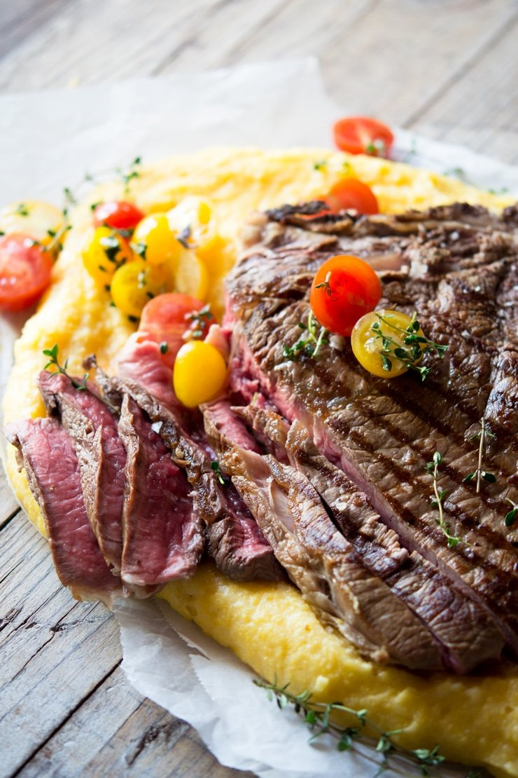 A side view of a florentine steak cut into slices (rare) topped with cherry tomatoes