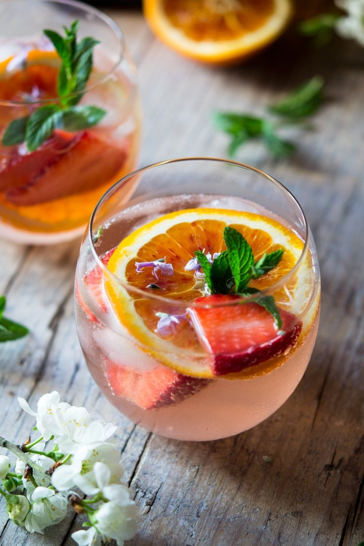 A close up shot of a cointreau rose cocktail garnished with mint leaves, orange and slices of strawberry