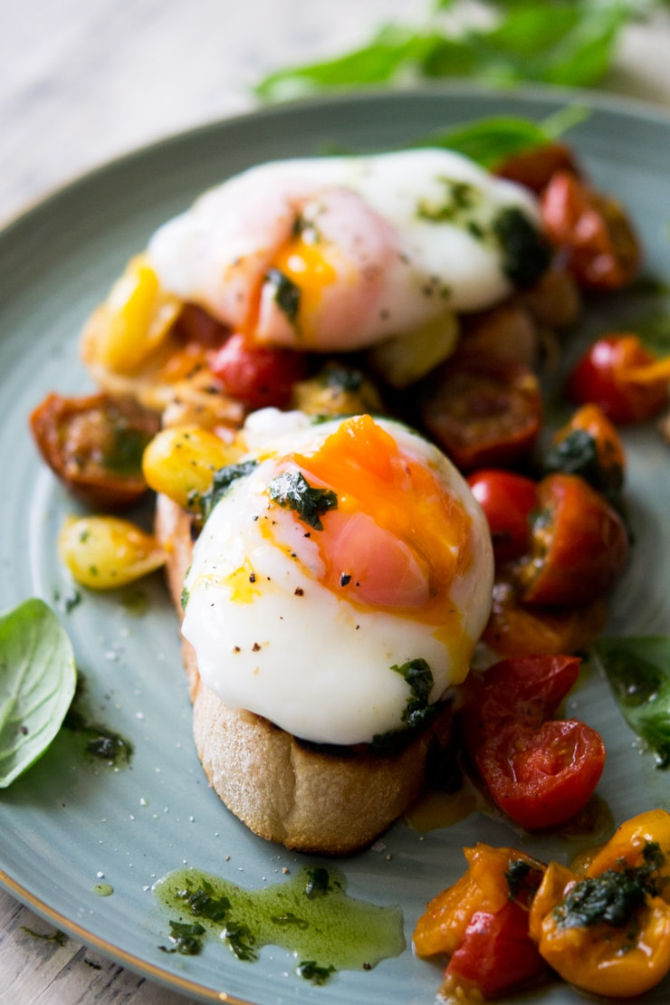 A close up of a oozing poached egg sitting on top of tomato breakfast crostini