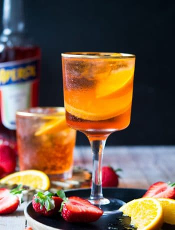 An aperol spritz cocktail in a wine glass with strawberries and oranges
