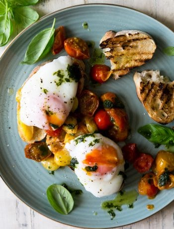 An overhead shot of sauted tomato breakfast crostini topped with poached eggs on a plate