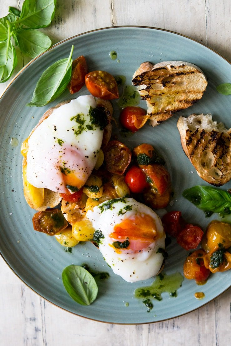 AN overhead shot of sauteed tomato breakfast crostini with poached eggs on top and scattered with basil