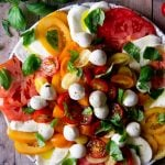 An overhead shot of a caprese salad with vibrant coloured tomatoes