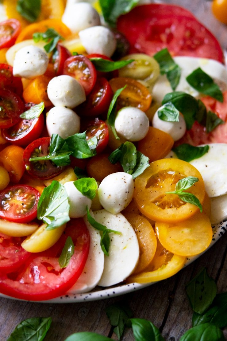 A close up of a a classic caprese salad with different coloured tomatoes
