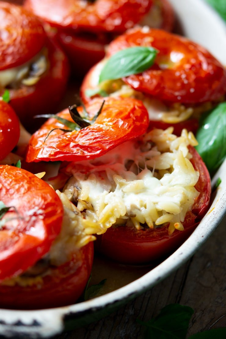 A close up of stuffed tomatoes in a baking dish filled with pasta and stretchy mozzarella cheese