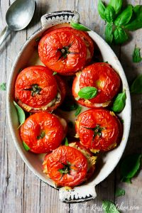 A pin image of baked stuffed tomatoes in a baking dish