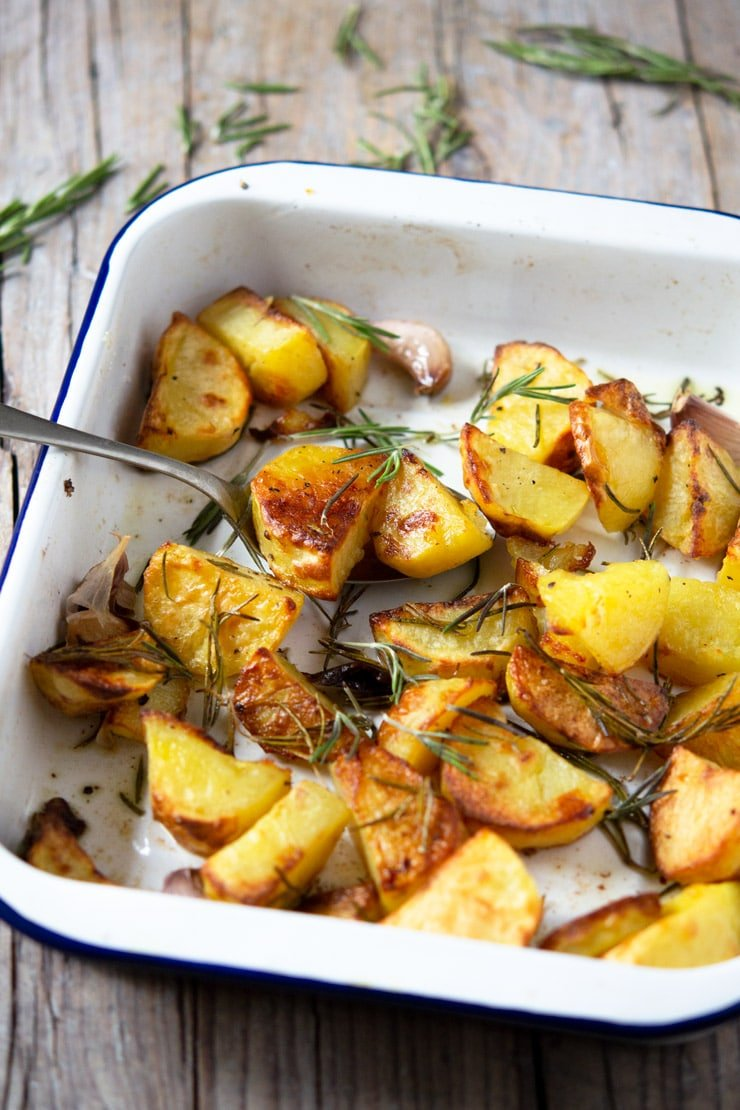 Italian roast potatoes in a baking tray with rosemary and garlic