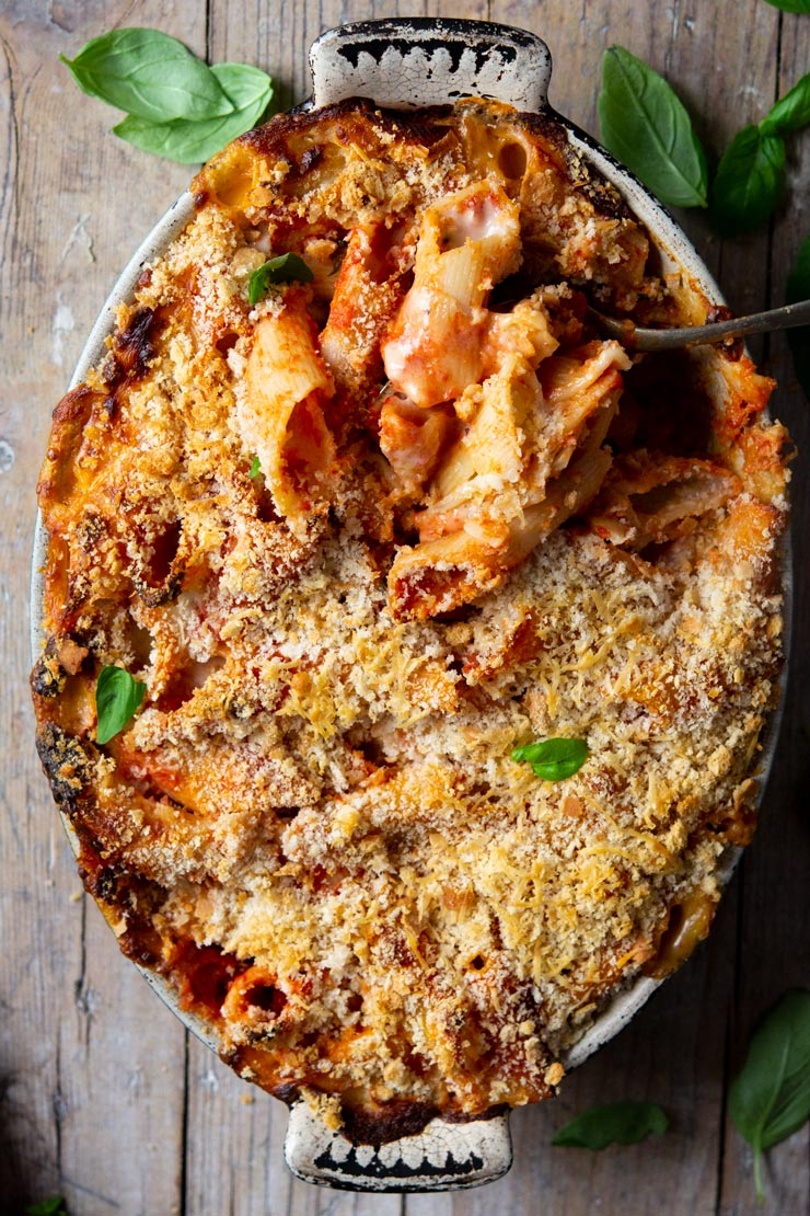 A tomato pasta bake in a baking dish topped with breadcrumbs