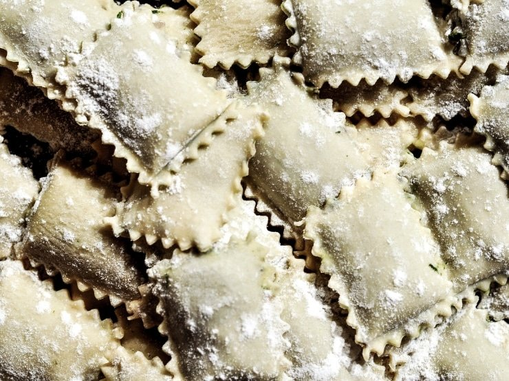 A close up of ravioli cut out perfectly with a ravioli stamp, one of the essential kitchen tools for Italian cooking