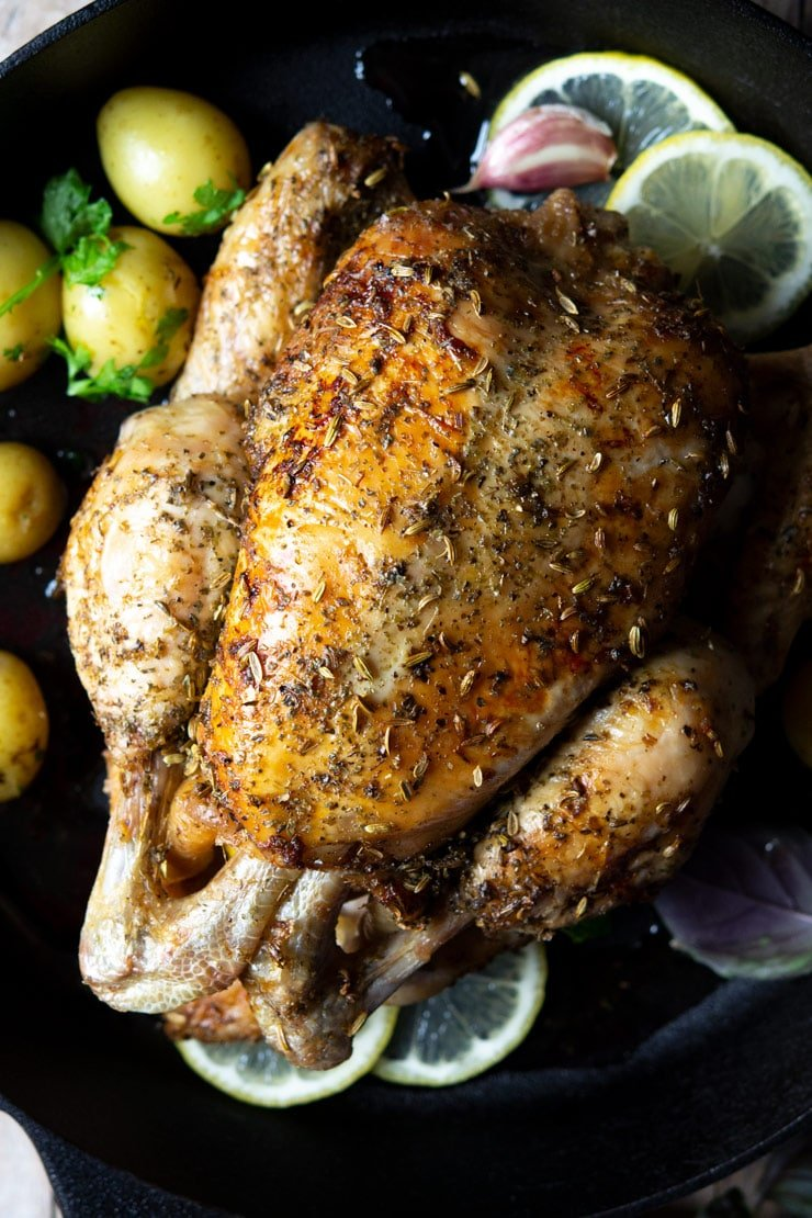 A close up of a lemon roast chicken in a cast iron skillet with potatoes and garlic