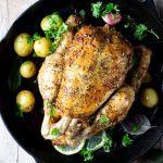 A lemon roast chicken in a cast iron skillet