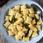 A square image of gnocchi with brown butter sage sauce