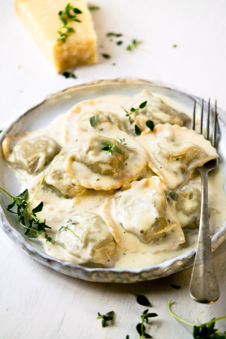 Close-up view of Stuffed Mushroom Ravioli with Parmesan Cheese on a Plate with a Fork