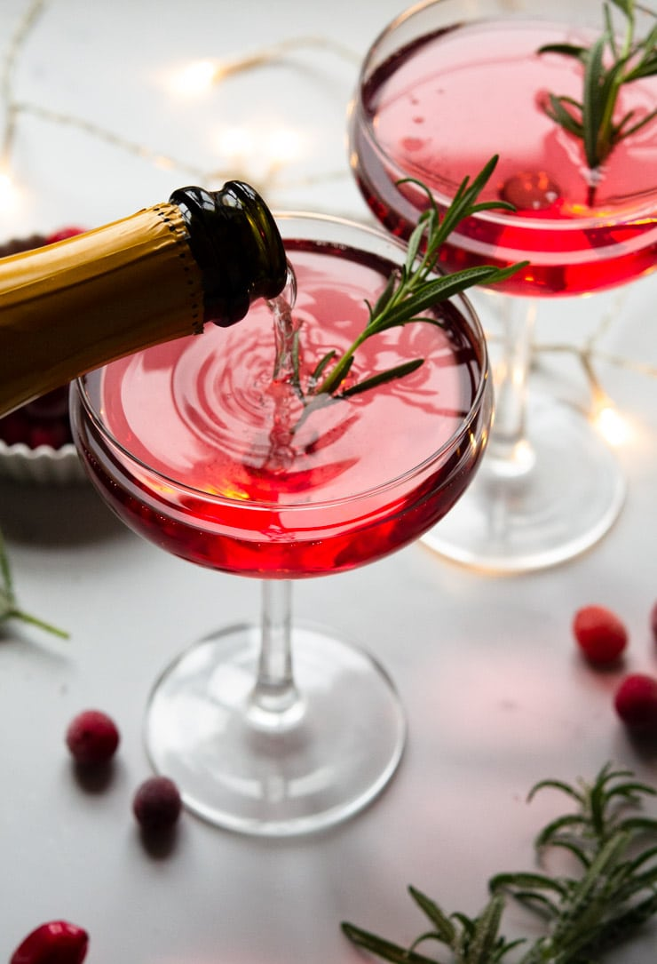 Someone pouring a Christmas cocktail topped with rosemary