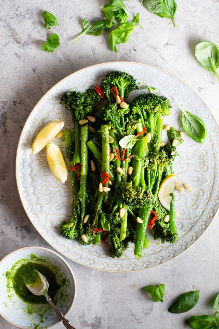 An overhead shot of sauteed broccolini on a plate with lemon wedges, pine nuts and chilli