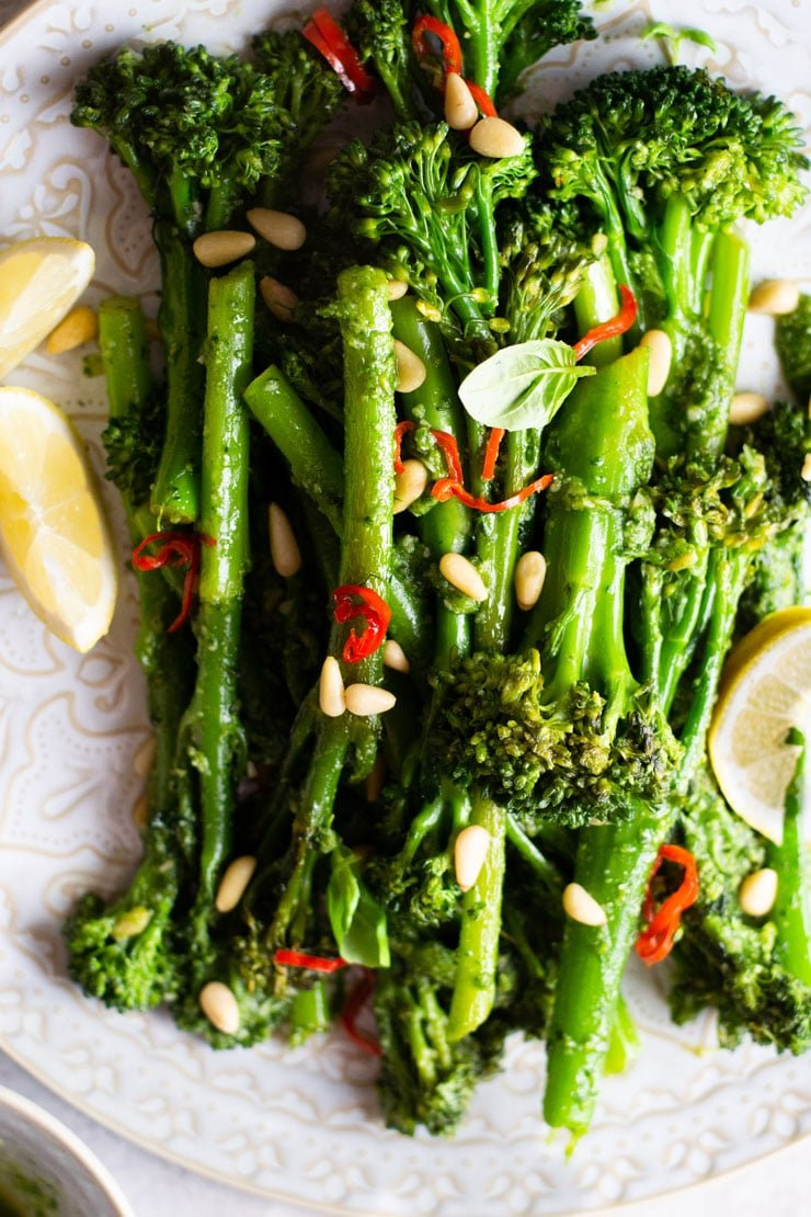 A close up of sauteed broccolini on a plate topped with pine nuts and chilli
