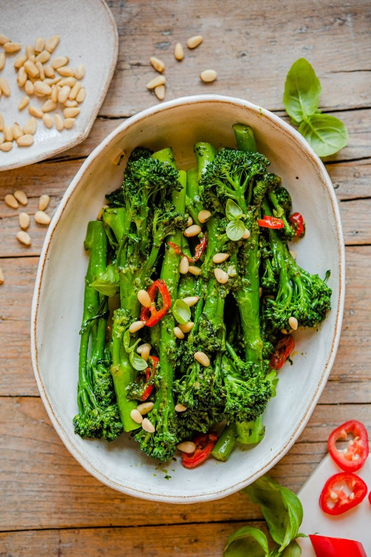 An overhead shot of sauteed broccolini in a serving bowl with pine nuts on top