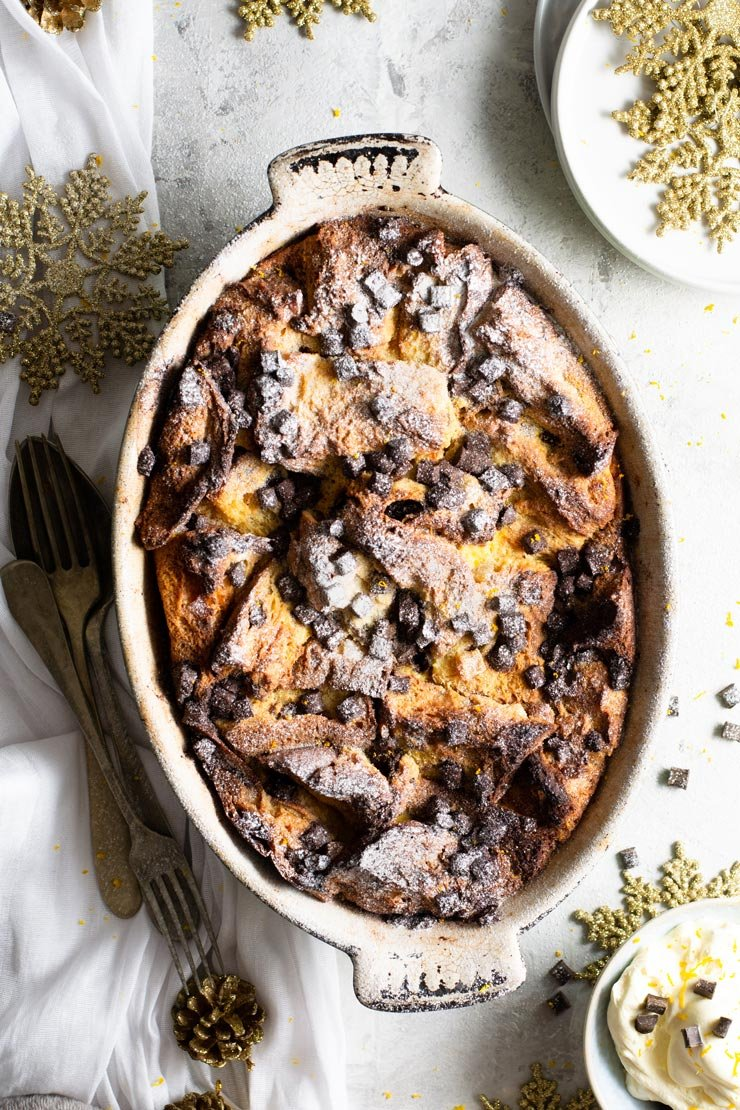 An overhead shot of panettone bread pudding in an oval baking dish with fresh cream at the side