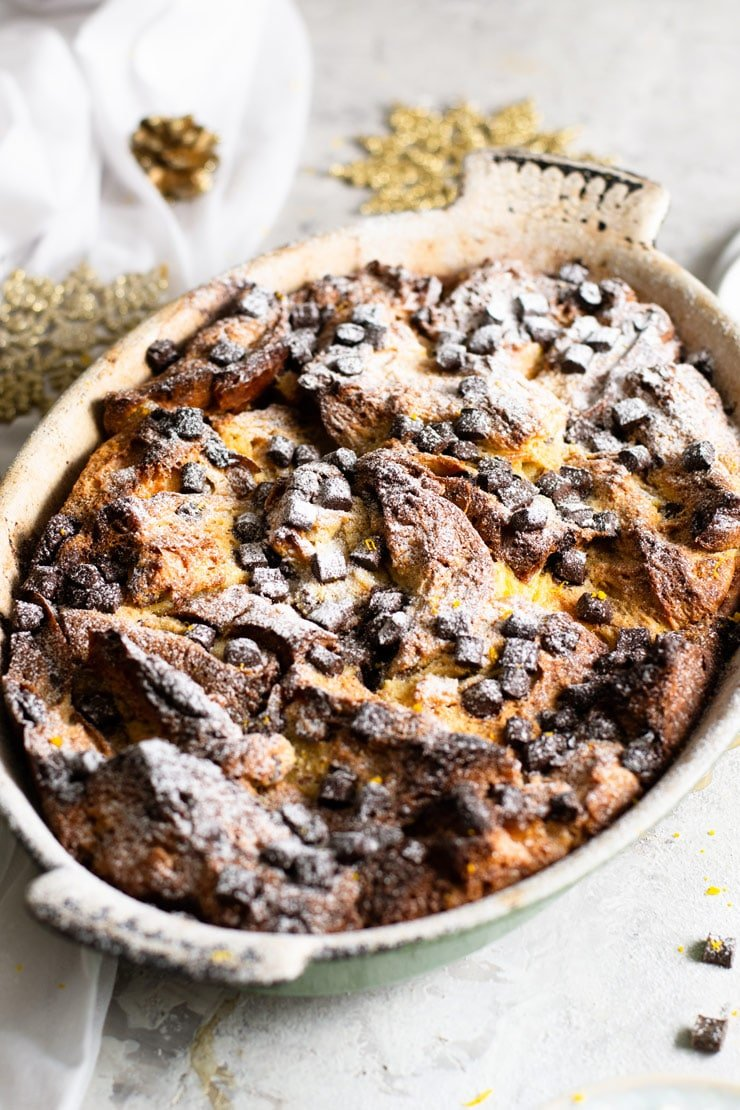 A close up of a panettone bread pudding in a rustic oval baking dish topped with chocolate chips and powdered sugar