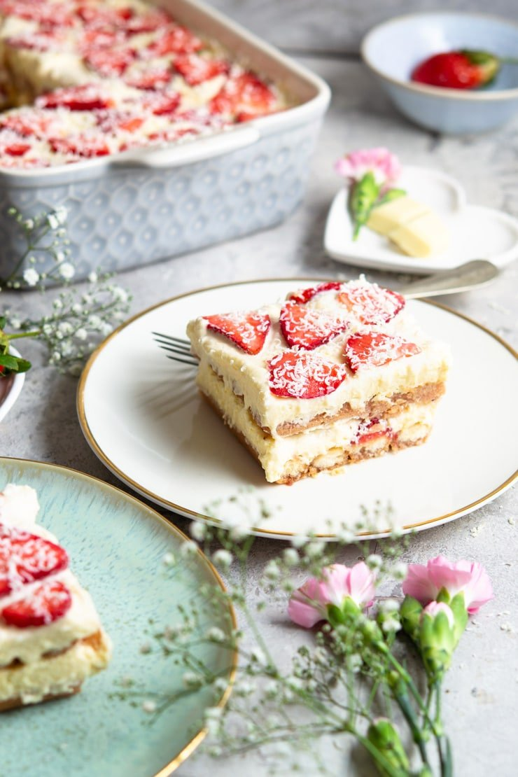 A slice of strawberry tiramisu on a white plate with flowers scattered around
