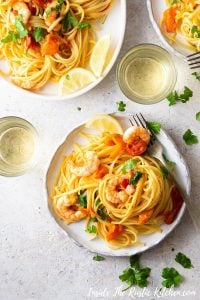 An overhead shot of shrimp linguine on a plate with lemon wedges