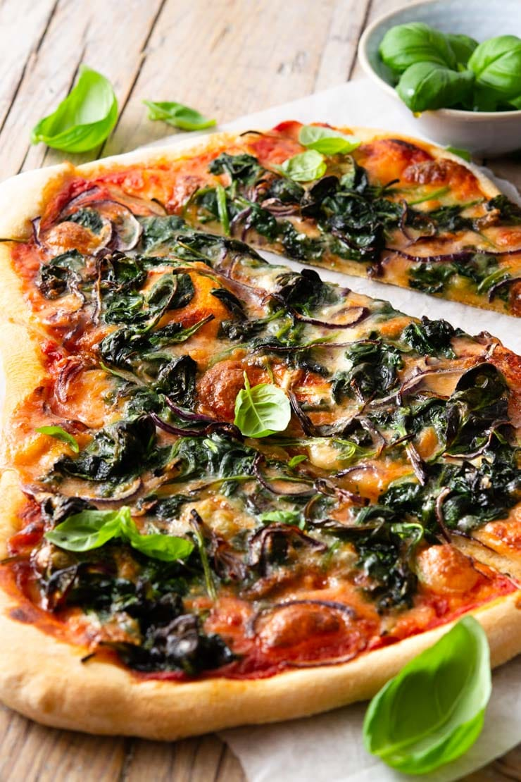 A close up of a spinach pizza cut into slices with gorgonzola cheese and red onion