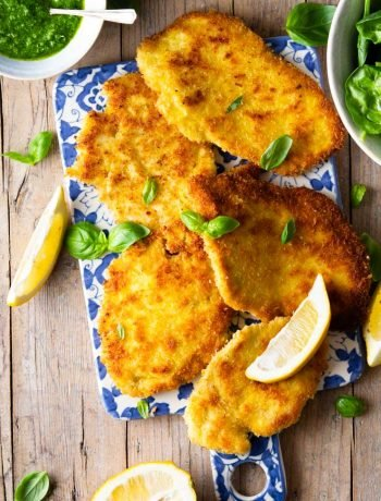 Italian chicken cutlets on a board with lemon wedges