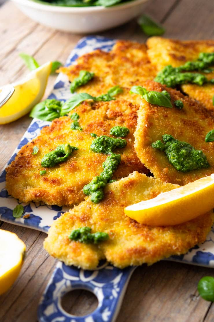 A side shot of breaded chicken cutlets on a blue serving board drizzled with pesto and lemon juice