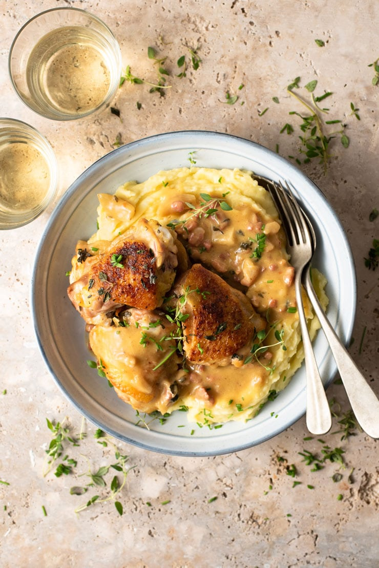 An overhead shot of creamy Tuscan chicken in a blue bowl with mashed potatoes and glasses of white wine