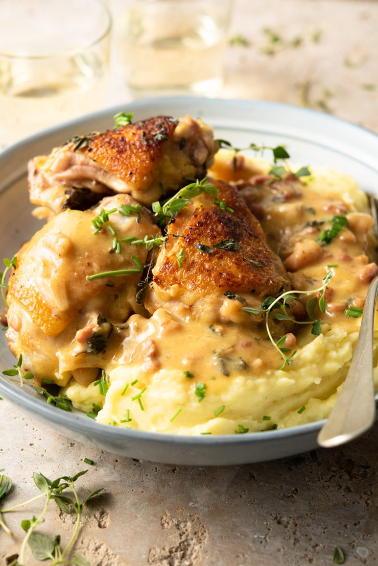 A side shot of creamy Tuscan chicken in a blue bowl with mashed potatoes